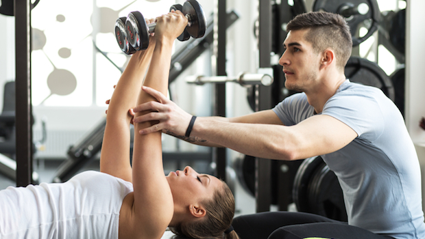 a fitness trainer helping a women in lifting weight